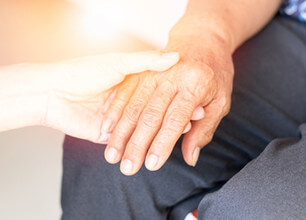 介護士と高齢者の手